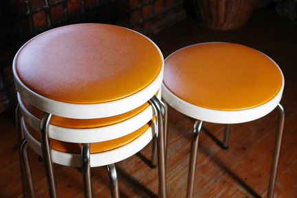 detail of set of 4 orange seated Chair Centre stacking stools