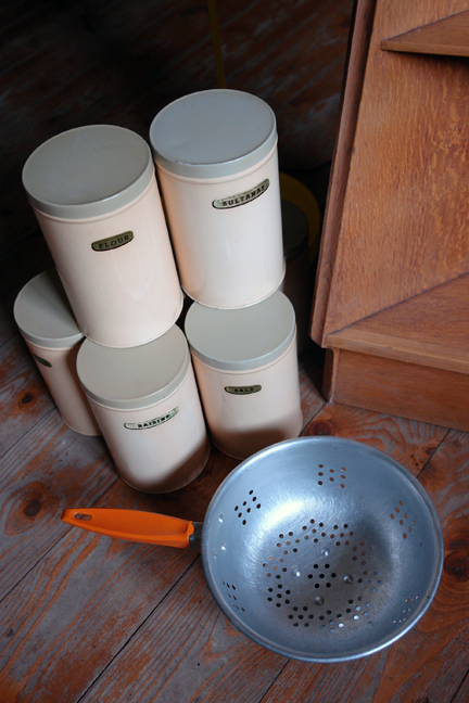 set of 1950s cream coloured kitchen storage tins with an orange-handled aluminium colander