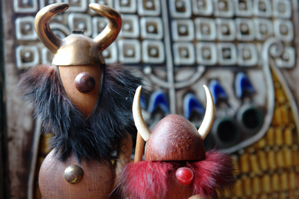 pair of vintage Viking noggin figures in front of a Lisa Larson ceramic tile of a Viking ship