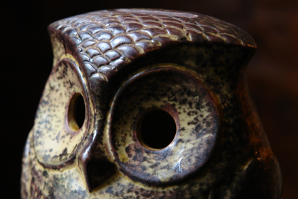 detail from a brown vintage pottery money box in the shape of an owl