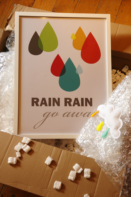 large cardboard box opened revealing rain rain, go away poster and mobile