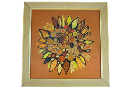 framed & glazed vintage wool work in shades of orange featuring a sunflower