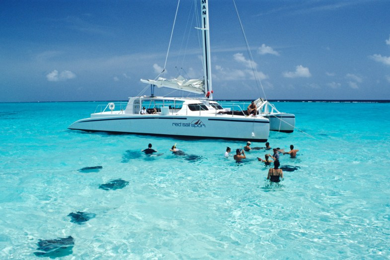 Tourists swimming with sting-rays, Stingray City, Grand Cayman, Cayman Islands, Caribbean, Central America