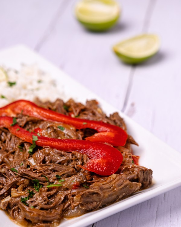 Cuban ropa vieja. Shredded beef in a tomato sauce. Plated with white rice on a white place and white wooden table background.