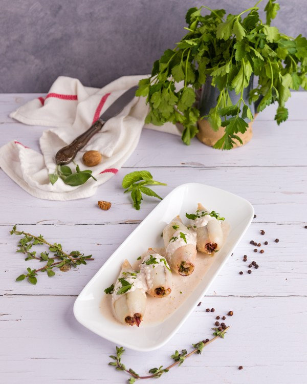 stuffed squid from the book of sent sovi. squid are set on a single layer on a plate, covered in almond sauce and sprinkled with parsley. the place is placed on a white wooded surface and is surrounded by herbs and spices.