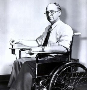 George Klein sitting in his prototype electric wheelchair, c. 1953 (Courtesy National Research Council of Canada Archives) NB: In 1930 a lightweight folding wheelchair that used tubular steel and mechanical components was developed. The chair was developed by two Americans named Harry Jennings and Herbert Everest. The company that they founded, E&J, took off during the early 1940's due to the war. Some people began fitting electric motors to the chair and a firm in Chicago offered motors that attached to the E&J chairs. While it was a very innovative concept, these motors did not last for long and were very prone to mechanical failure. After trying many of the drive systems that were commercially available, the Canadian government asked George J. Klein to create a reliable and durable system. Klein began working on his own electric control system for the E&J chair in 1950. Klein felt that since the E&J chair could be easily and efficiently reproduced that it would be a disservice to his government and those who would use his chair to not use it. After several years of testing Klein revealed his electric propulsion system which would completely revolutionize the wheelchair. Many of his innovations, including the joystick control, can still be seen in today's power chairs. By 1955 the popularity of the chair had grown in both the US and Canada. It was used by veterans and civilians alike. To help with the production and improve publicity, Canada allowed the US to begin manufacturing the system.
