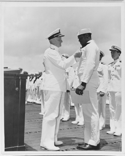 Admiral Nimitz awards the Navy Cross to SC2c Doris Miller for heroism on USS West Virginia (BB-48). He was later killed. This ceremony and other awards and commendation letters were give by the admiral onboard USS Enterprise (CV-6) at Pearl Harbor, March, 1942.