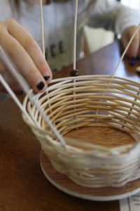 A child's hands are threading beads onto the upright frame of a basket in the process of being woven