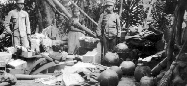 "Hand-written caption on the back of the photo: ""Communist woman with all the stolen goods."" Items include clay jugs and corn grinders."
