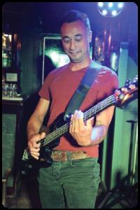 man die basgitaar speelt tijdens muziekquiz Hitsz