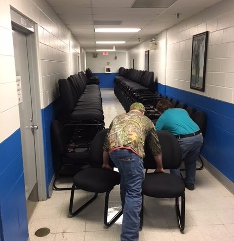 custodial workers moving chairs