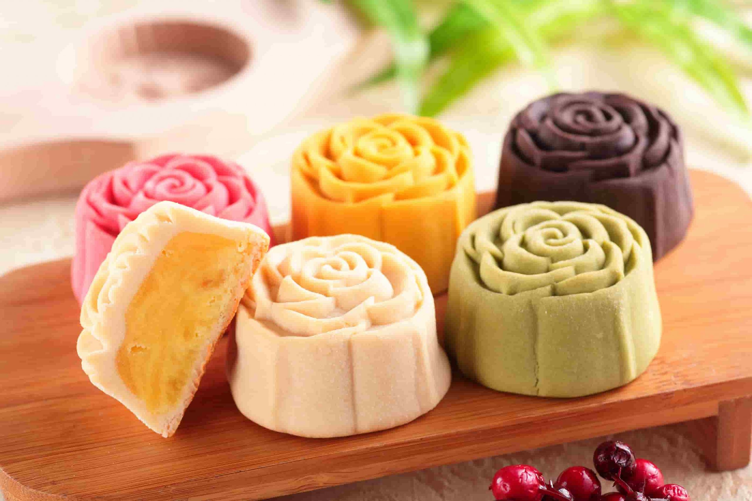 Colorful mooncakes made by crystal rice dumpling machine on a wooden tray