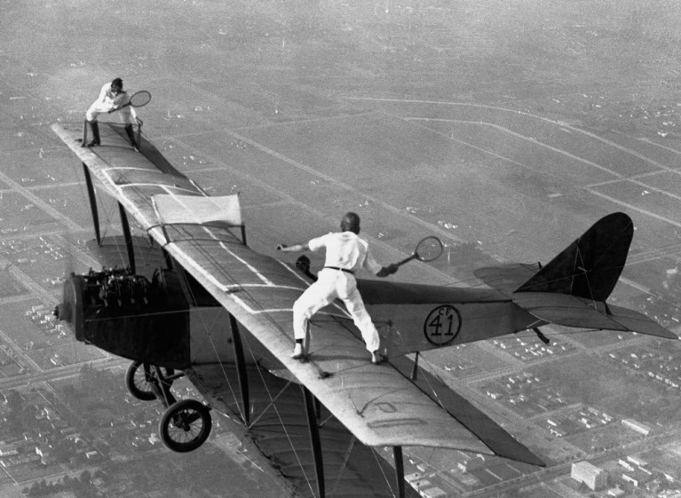 Image about Two Daredevils Playing Tennis on Flying Airplane Wings
