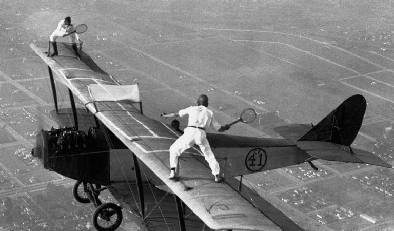 Two Daredevils Playing Tennis on Flying Airplane Wings: Fact Check