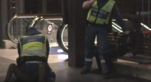 Image of Two security guards detaining the two boys at Malmö train station