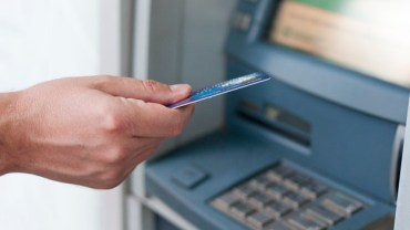 Hand inserting ATM card into bank machine to withdraw