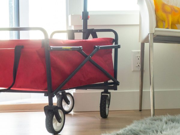 Red foldable wagon in bright apartment living room, with dinosaur toys sitting on a chair. Grey faux fur rug on the floor.