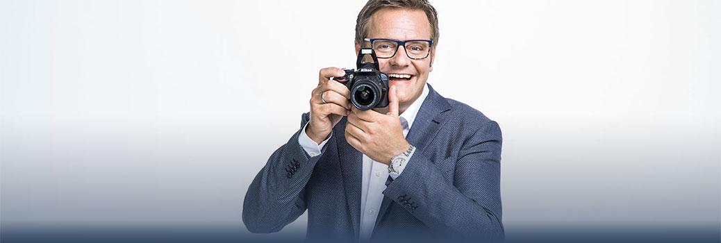 Unternehmer Robert Hartlauer lacht und fotografiert in die Kamera