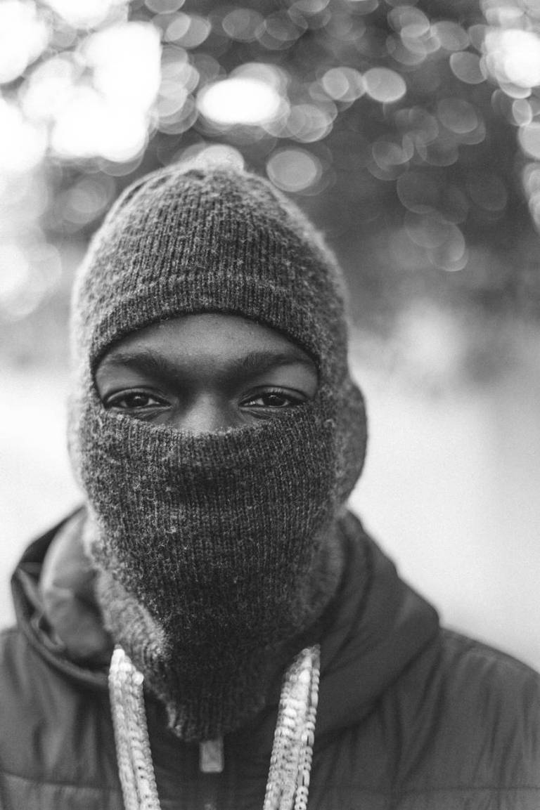 monochrome photo of person wearing balaclava