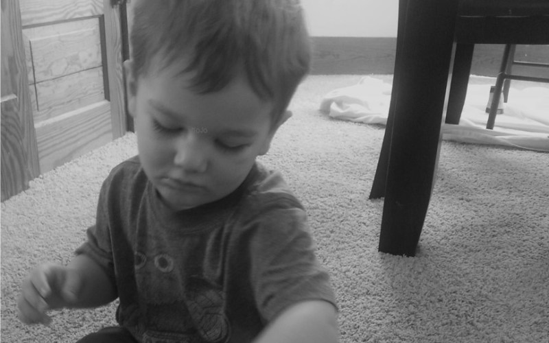 This image shows our toddler son enjoying some card drop fun. It's one of the great toddler activities using fine motor skills that we share here on the blog.