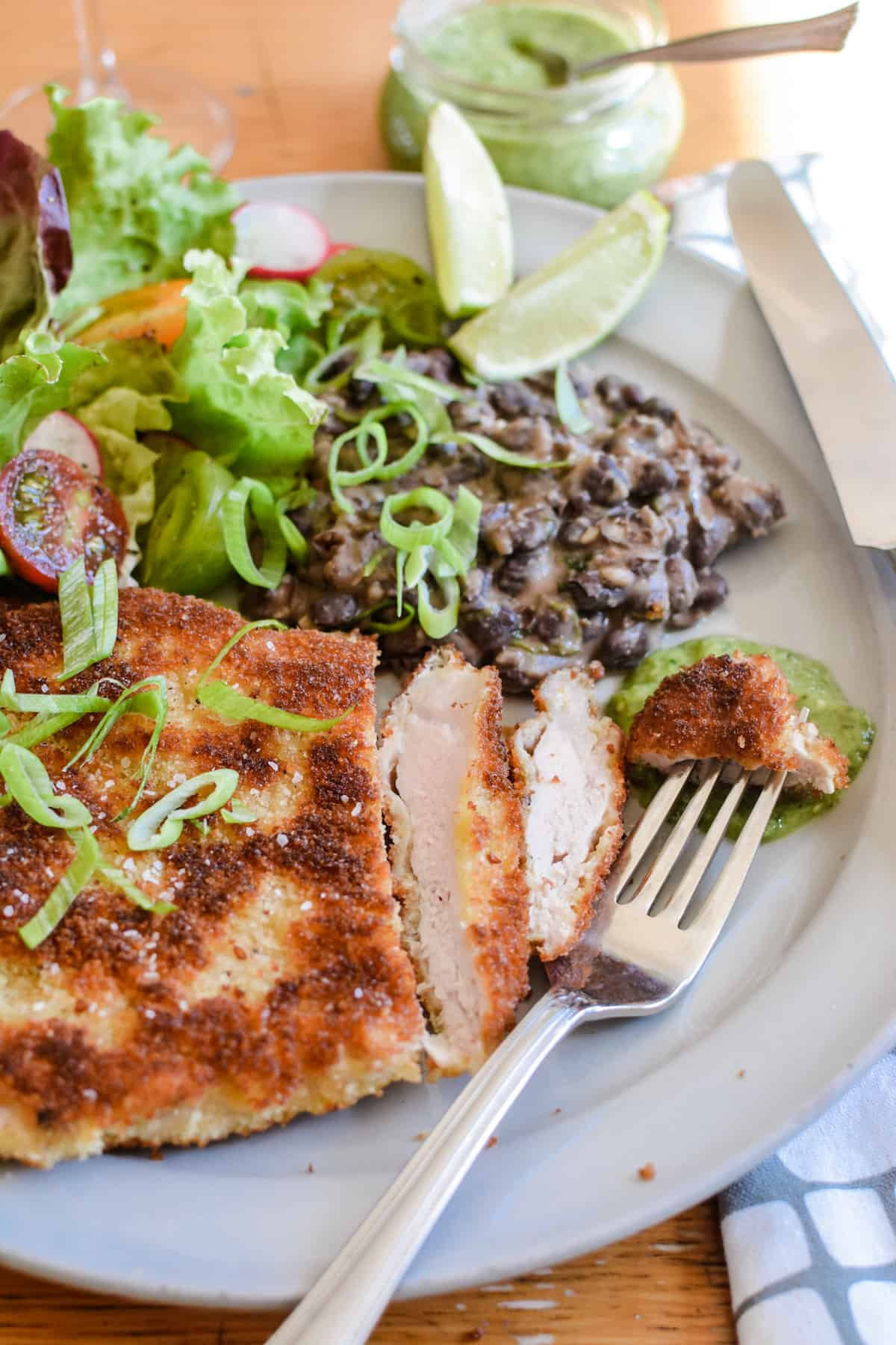 Pork cutlet sliced on a plate with green sauce, black beans, and a salad with lime wedges and a piece on a fork.