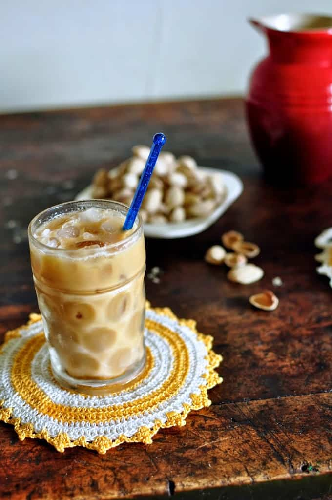 Iced coffee sitting on a wooden table on top of a yellow and white doily.
