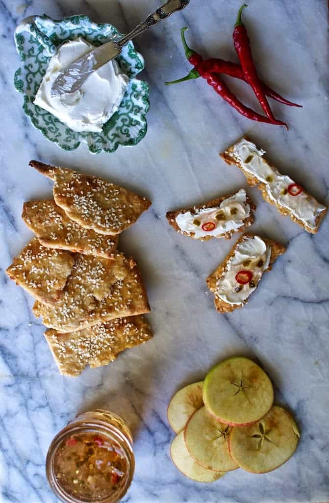 A marble table with a green dish of cream cheese, fresh cayenne peppers, and homemade crackers and jelly.