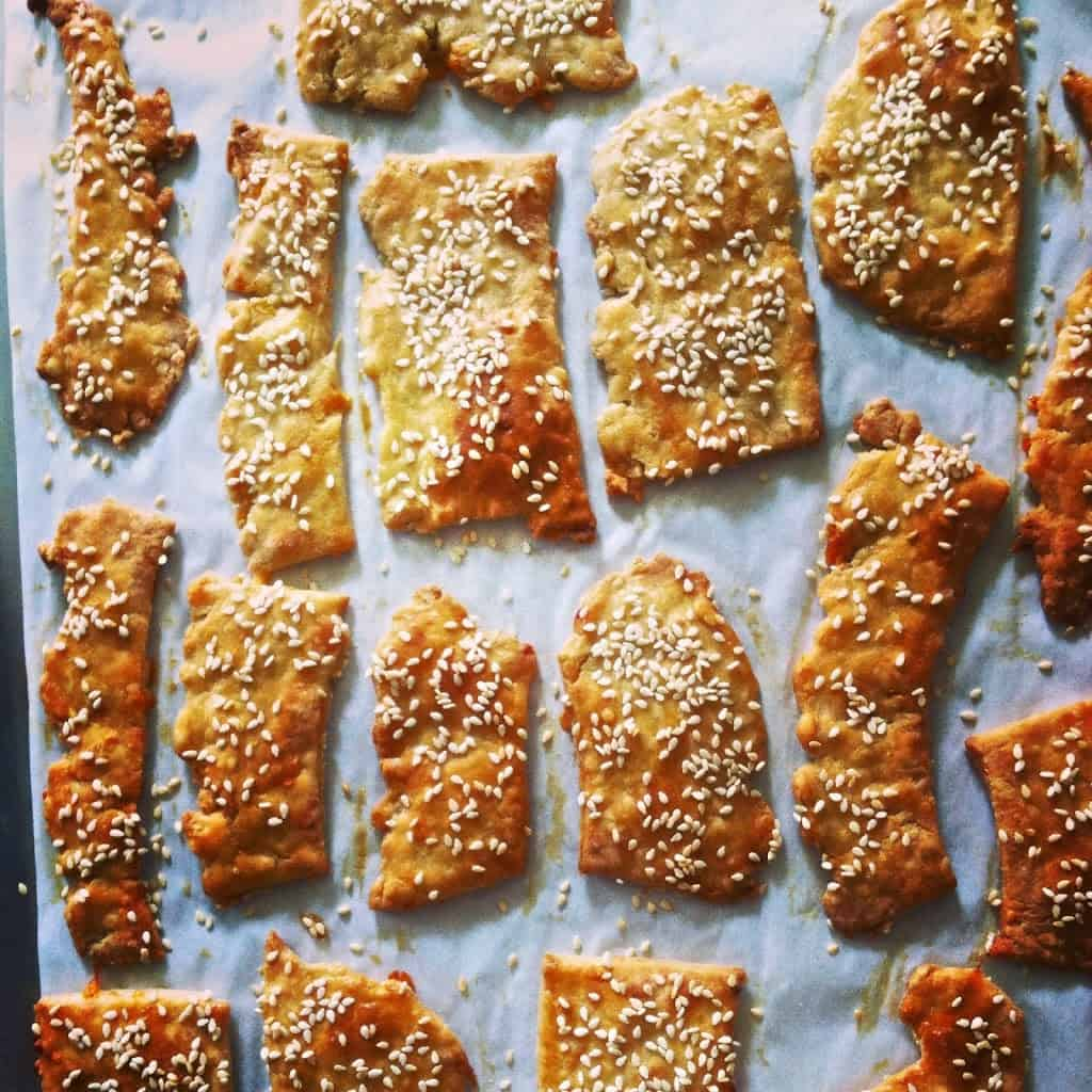 Several homemade cheddar crackers with sesame seeds sitting on a piece of white parchment paper.