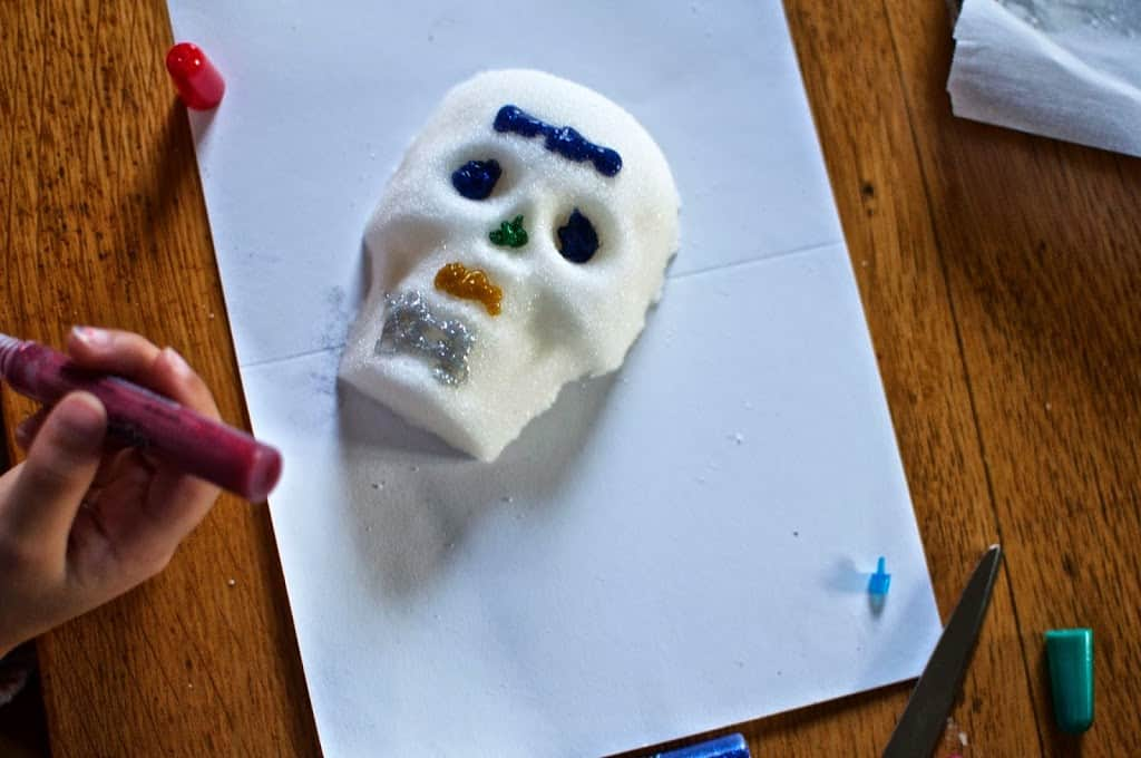 A partially decorated sugar skull sitting on top of a white piece of paper on a wood table.