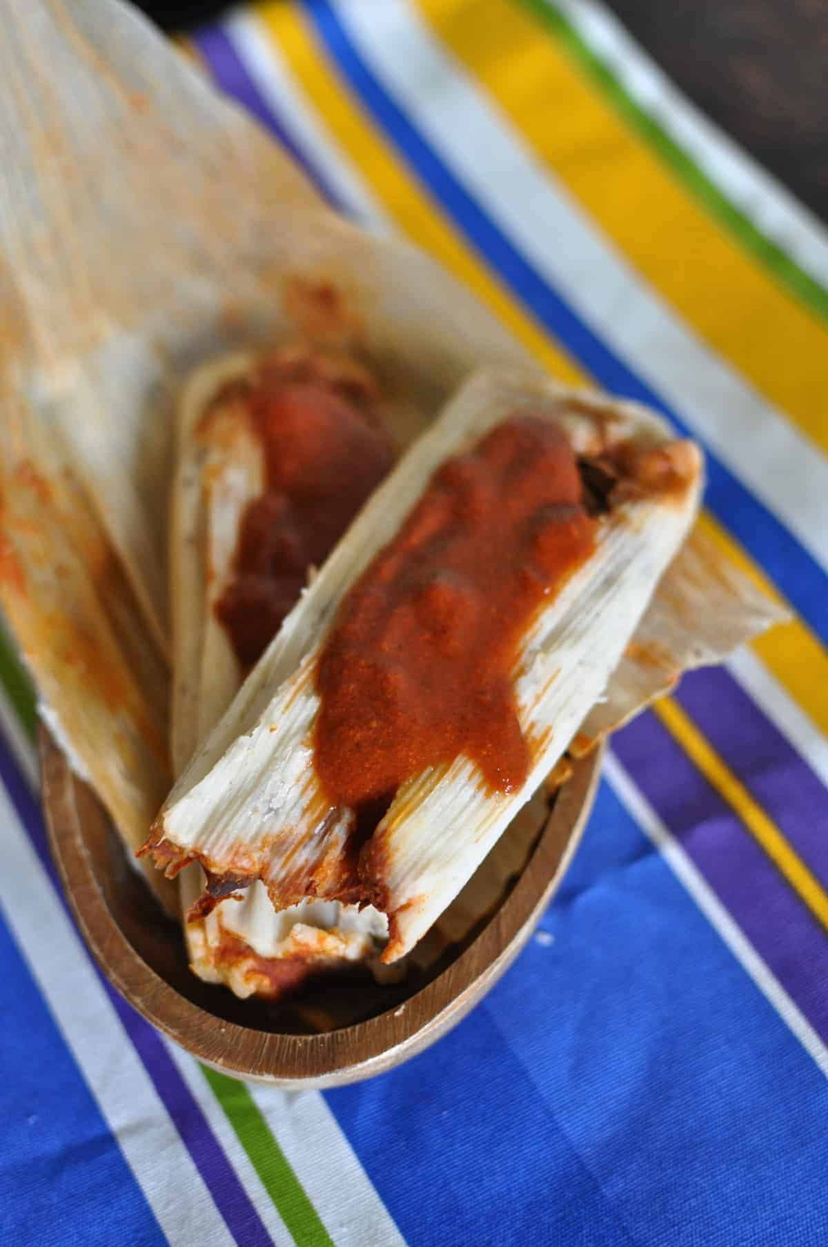 Two pork tamales with mole Colorado sitting on a corn husk on a wood bowl on top of a blue striped kitchen towel.