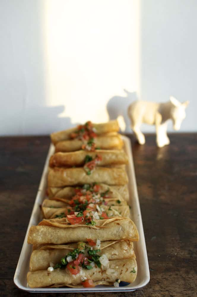 A tray of taquitos topped with chopped tomato, cilantro, and onions sitting on a wooden table.