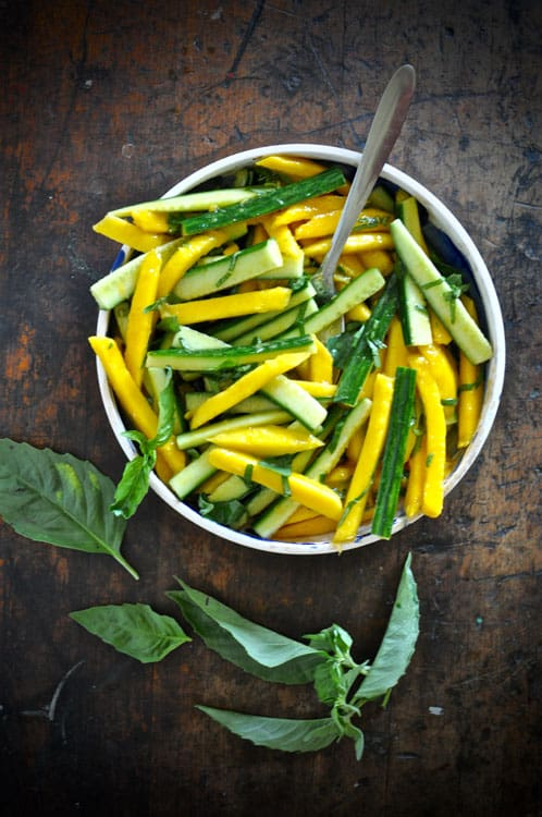 A shallow bowl filled with Mango-Cucmber Salad with Cayenne Vinaigrette on a wooden table with basil leaves.