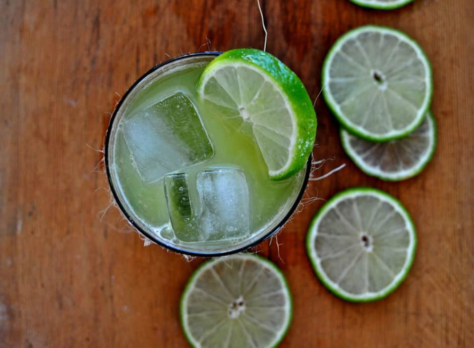 A glass of Mango Lime Agua Fresca with ice cubes and lime slices sitting on a wooden table.