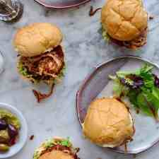 These chorizo burgers are made with Mexican chorizo and ground beef then topped with smashed avocado and a generous pile of crispy fried red onion strings.
