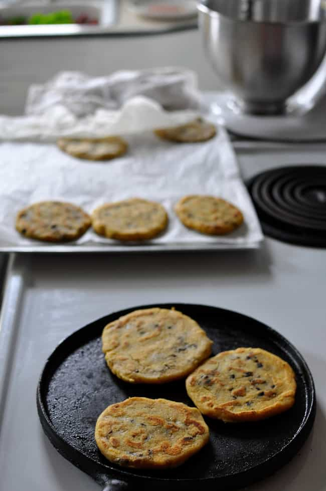 A pan on the stove top making black bean pupusas with a baking sheet of more pupusas in the background.
