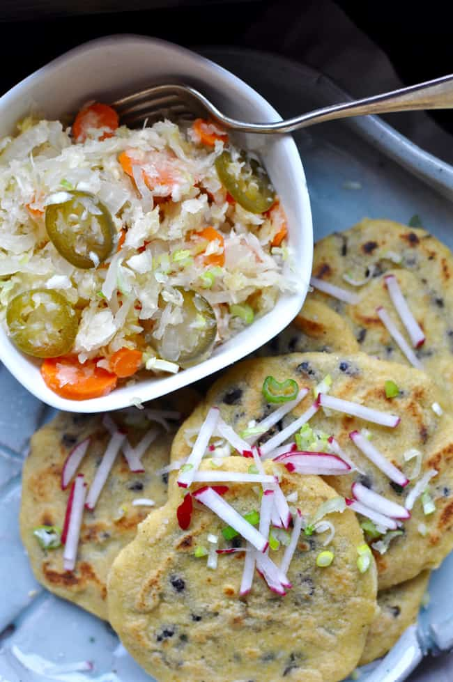 A plate of black bean pupusas sitting next to a small bowl of lime curtido with a fork sticking out of the bowl.
