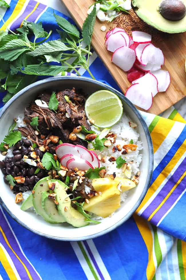 A bowl of rice topped with black beans, avocado slices, pineapple slices, and beef.