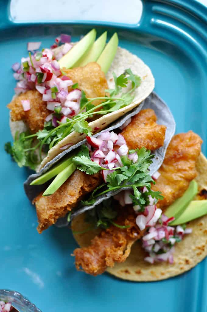 Three Beer-battered fish tacos with radish salsa on a blue platter.