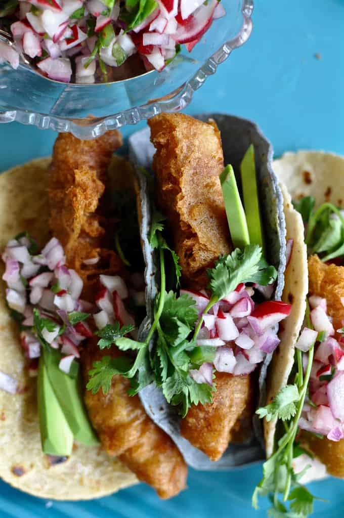Close up of crispy fish tacos on a blue platter.