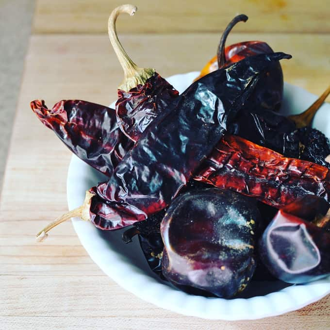 Several different dried chiles sitting in a small white bowl on a wooden cutting board.