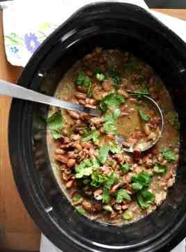 Crock pot with frijoles borrachos and cilantro.