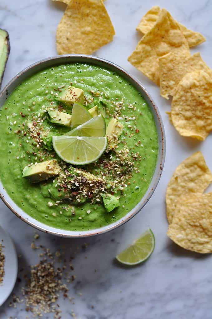 Tomatillo Avocado Salsa Recipe in a large bowl with hunks of avocado and lime slices on top. There are several chips laying around the bowl.