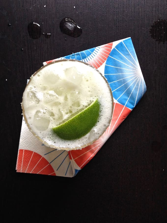 A glass with ice and a margarita in it with a lime wedge on top sitting on a colorful napkin.