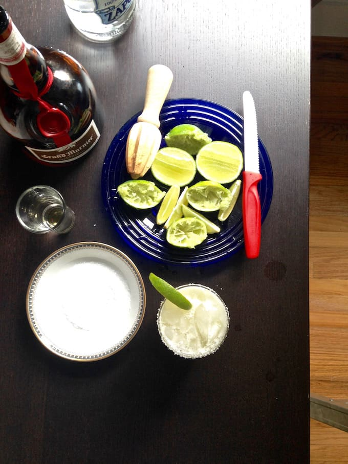 A dark wood table with liquor bottles, a shot glass, a plate of limes, and a margarita.