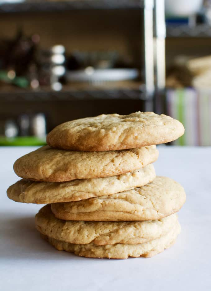 6 light brown cookies stacked on each other sitting on a white table.