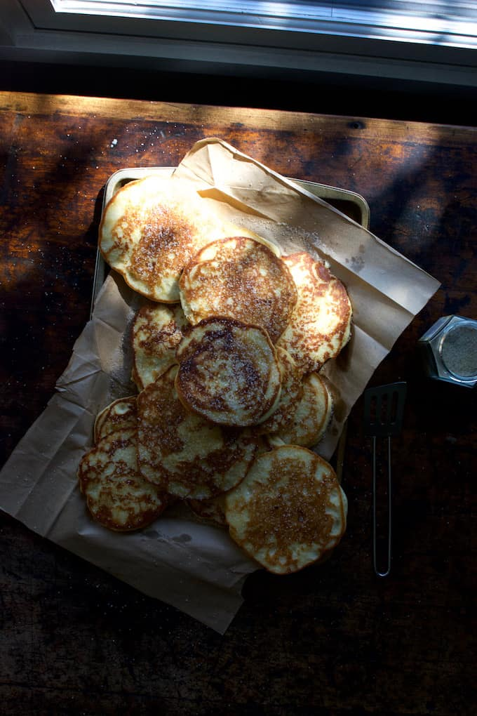masa harina pancakes on a piece of parchment paper on a baking sheet with sugar sprinkled on top sitting on a wood table.