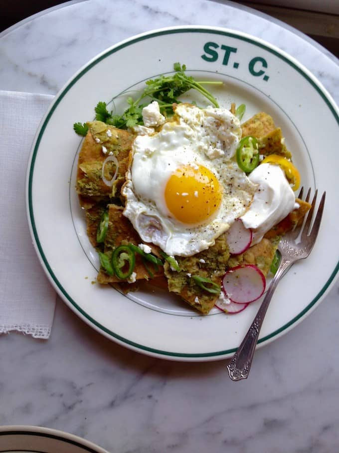 A plate of chilaquiles with a fried egg on top sitting on a marble table with a fork on the plate.