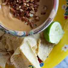 Overhead image of a bowl of salsa de cacahuate or creamy peanut salsa with chips and lime on the side.