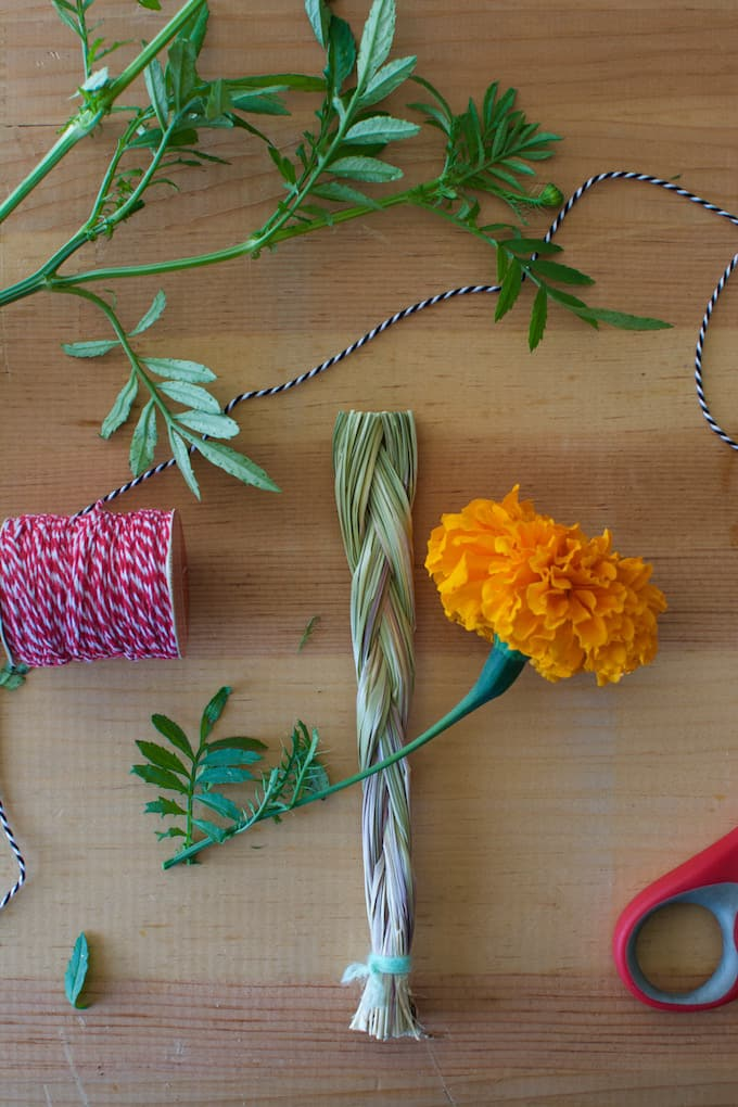 Dried sweetgrass, red and white string, and a marigold flower sitting on a wooden table.