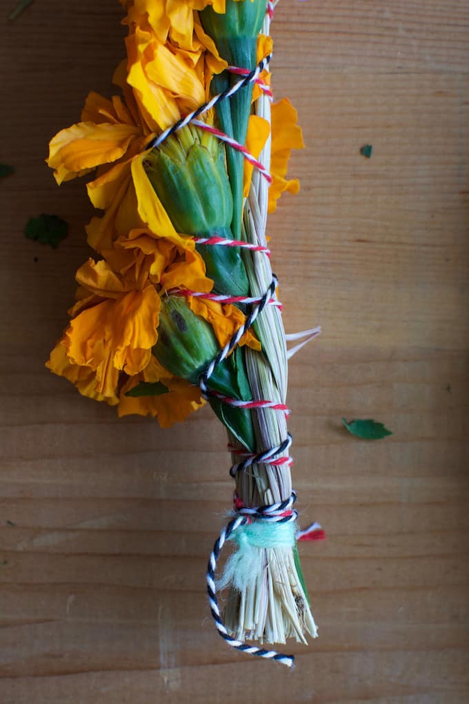 Marigold flowers wrapped around dried sweetgrass and tied with red and white string.